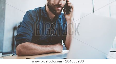Young businessman using smartphone at office and making notes.Blurred background.Horizontal wide.Cropped