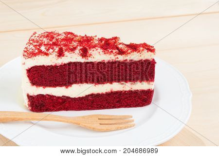 Red Velvet Cake sliced in piece on white plate with wood fork on light wooden background and copy space for celebrate X'mas season occasion Valentines day birthday or special holiday events