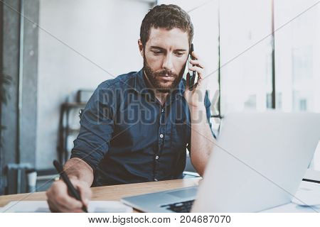 Pensive businessman using smartphone at office and making notes.Blurred background.Horizontal