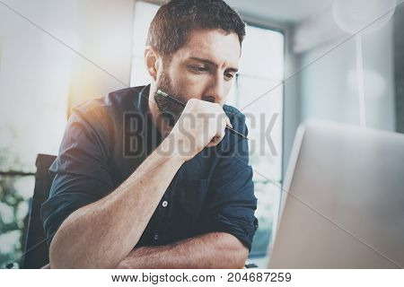 Hispanic young businessman thinking new business idea while working at sunny office.Blurred background. Horizontal.