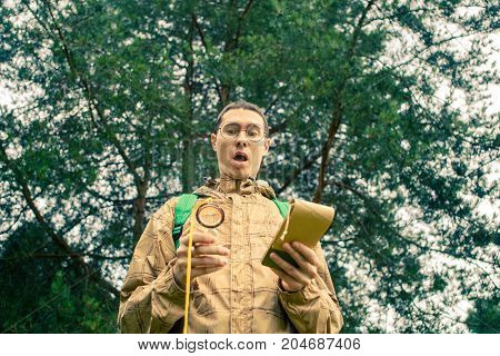 Picture of brunet with compass and notepad in autumn forest