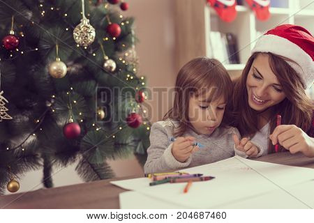 Mother and daughter having fun drawing with wax colors and enjoying winter holidays