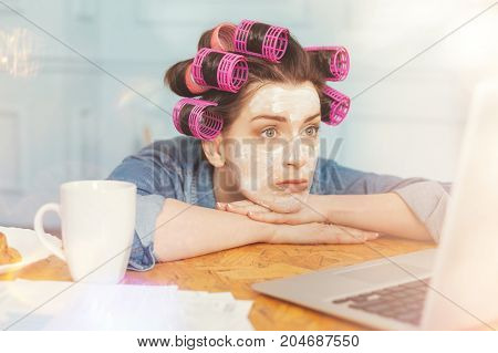Be serious. Pretty brunette having face pack holding hands on the table while looking at computer