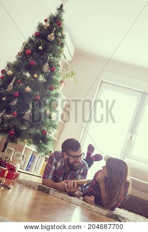 Beautiful young couple lying on the living room floor next to a nicely decorated Christmas tree exchanging Christmas presents