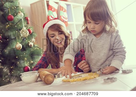 Young mother and daughter baking Christmas cookies and having fun