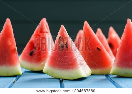 Helthy refreshing summer snack. Fresh bright juicy watermelon slices with seeds on blue background closeup