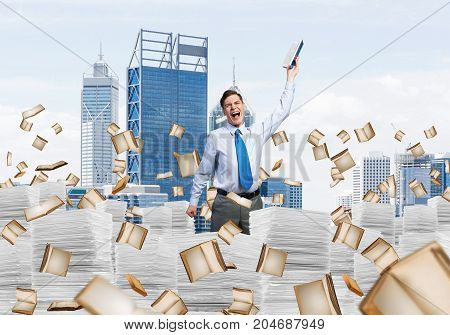 Businessman keeping hand with book up while standing among flying books with cityscape on background. Mixed media.