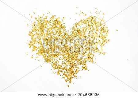 Heart made of golden confetti tinsel on white background. Flat lay top view. Minimal love concept.