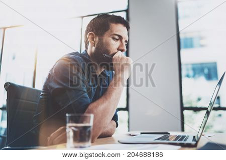Attractive businessman working at sunny work place on laptop while sitting at the wooden table.Man using smartphone and making notes.Blurred background.Horizontal