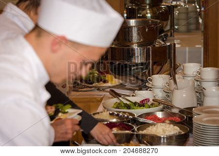A cook is preparing a food buffet in a restaurant during a festive event with assorted salads