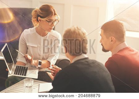 Working together. Beautiful confident professional businesswoman sitting opposite her colleagues and pointing at the laptop screen while showing a presentation