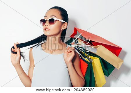 Portrait Of Attractive Asian Woman In Sunglasses And Shopping Bags