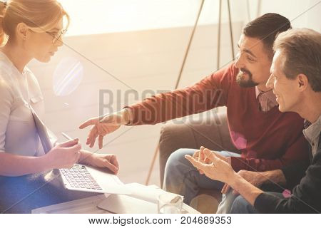 Great mood. Joyful happy nice men sitting together and smiling while looking at the laptop screen