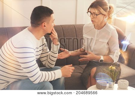 Physiological help. Sympathetic professional female psychologist discussing a problem with her patient and giving him advice while trying to help