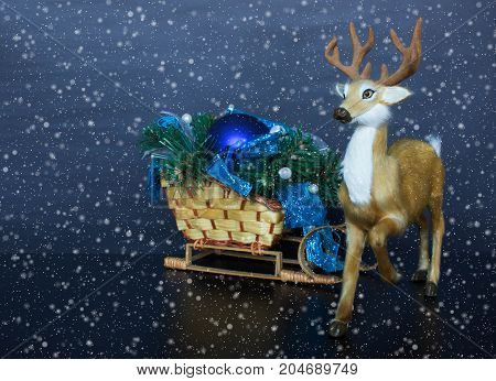 Christmas toy deer with wicker sled, fir branches and new year tree ball on dark blue or black background. Snowfall overlay on holiday decorative installation.