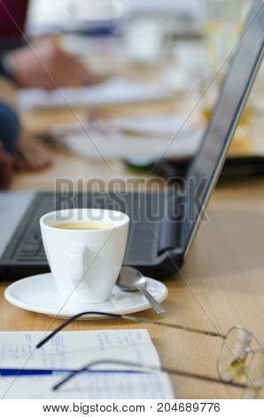 Laptop photo with cup of coffee and notepad on wooden table on business break meeting with blurred background