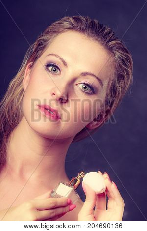 Smell elegance concept. Beautiful elegant blonde woman with holding perfume bottle studio shot on dark background