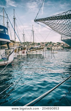 Sailing ships anchored in the harbor Trogit Croatia. Travel destination. Summer vacation. Travelling theme. Old photo filter.