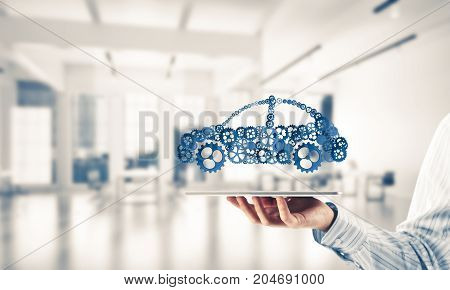 Car icon made of gears and cogwheels on white office background. Mixed media