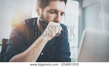 Pensive man using contemporary laptop at office.Blurred background.Horizontal.Flares