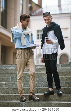 Modern communication for young men. Street style. Happy students outdoors, stylish youth, technology concept