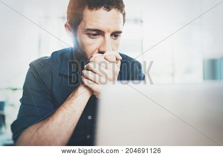 Businessman working at modern loft office.Pensive Man sitting and using contemporary laptop.Blurred background.Horizontal.