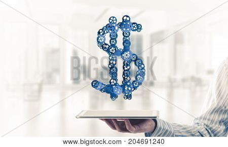 Close of businessman holding tablet pc with dollar sign made of gears. Mixed media