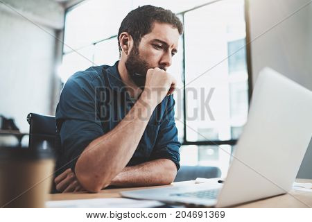 Young pensive man working at sunny office on laptop while sitting at wooden table.Businessman reports on notebook computer.Blurred background, horizontal