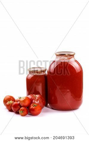 Banks with tomato juice and tomatoes on a white background