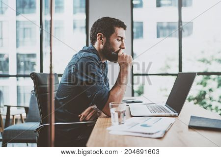 Young pensive coworker working at sunny work place loft while sitting at the wooden table.Man analyze document on laptop display.Blurred background.Horizontal