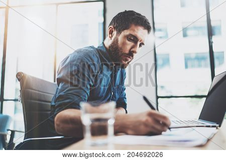 Young pensive man working at sunny loft office on laptop.Businessman making notes on paper documents reports.Blurred background.Horizontal