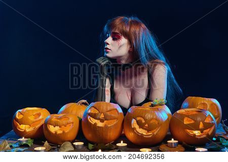 Woman with Halloween makeup sitting thoughtful at table with pumpkins over blue background