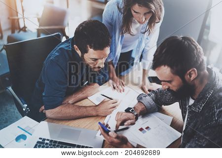 Teamwork working process.Group of young coworkers working together in modern office loft.Man using mobile phone.Blurred background.Horizontal
