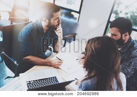 Teamwork brainstorming process.Young man working together with partners in modern office loft.Business meeting concept.Blurred background.Flares