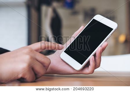 Mockup image of a woman's hand holding and pointing at white mobile phone with blank black screen in modern cafe