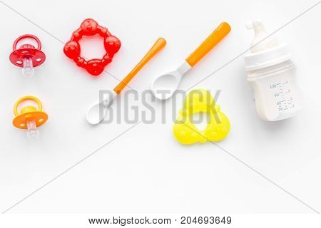 bottle with breastmilk and infant formula powdered healthy food, spoons and bib on white desk background top view mock-up