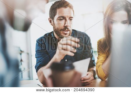 Teamwork concept.Coworking process at sunny office.Business team sitting at meeting room and making conversations.Horizontal.Blurred background.Flares