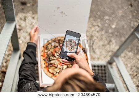 Social media influencer millennial hipster makes photo of his fresh hot out of the box delivery take away pizza on his smartphone for sharing online with followers