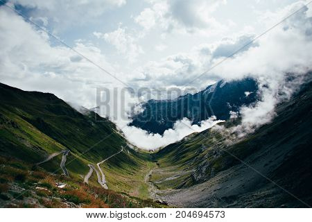Shot from top of Stelvio pass between Italy and Switzerland on sunny day standing above clouds and overlooking hairpins and sharp turns that lead to summit