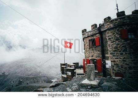 Brick made epic medieval old vintage refuge sanctuary on high altitude in italian alps covered in fog or cloud mist with red window shutters and swiss flag
