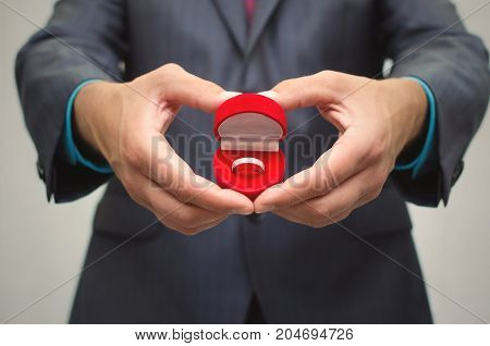 Love confession. Marriage proposal. Man in suit holds in hands heart shape box with wedding ring within.