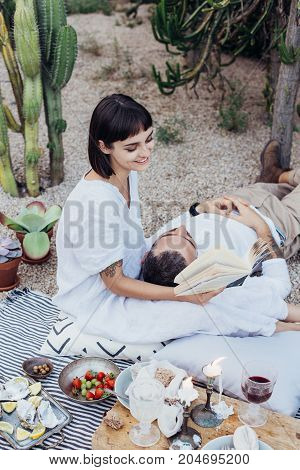 Beautiful petite brunette woman holds lover boyfriend on her lap and reads out loud from book in setting of cacti park decorated with pillows and candles for proposal
