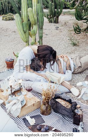 Cute beautiful couple of young millennial hipster people lay on picnic blanket spread in park and decorated in romantic way woman gives kiss to man laying on her lap