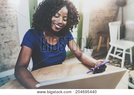 Smiling african american woman using laptop and smartphone while sitting at wooden table in the living room.Horizontal.Blurred background