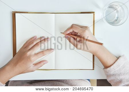 Top view. Happy Asian woman hands writing on notebook or diary with glass of water and white desk. Copy space.
