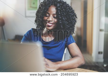 Closeup view of happy african american woman working laptop while sitting at wooden table in the living room.Horizontal.Blurred background