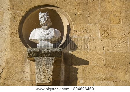 Photo of a stone sculpture with wall and sunlight