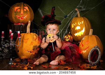 Little witch girl child laughing among pumpkins and candles