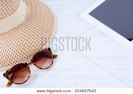 Portrait of sunglasses with a hat and digital tablet. Travel concept.