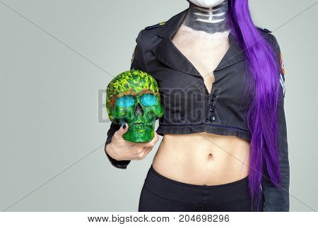 girl with makeup and purple hair holds a painted skull in her hand on a gray background. Mexican celebration of the Day of the Dead Dia de los Muertos and the Roman Catholic holiday All Souls Day